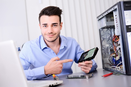handsome young computer technician repairing a desktop computer