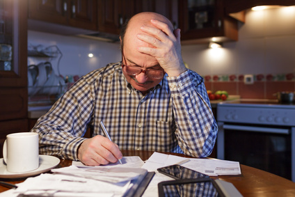 A man tiredly considers the family budget. Lack of money in the crisis.